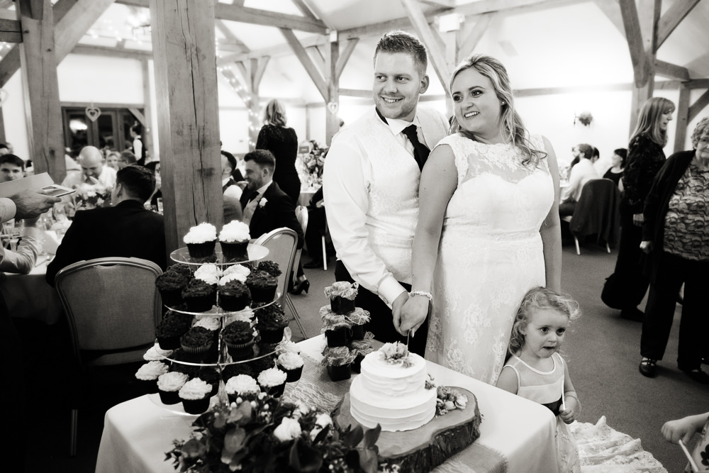 Cutting the cake at a Sandhole Oak barn wedding